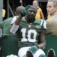 Photo -   New York Jets wide receiver Santonio Holmes (10) gestures to fans as he is carted off the field after being injured during the second half of an NFL football game against the San Francisco 49ers Sunday, Sept. 30, 2012, in East Rutherford, N.J. (AP Photo/Bill Kostroun)