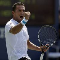 Photo - Victor Estrella Burgos, of Dominican Republic, reacts against Igor Sijsling, of the Netherlands, during the first round of the 2014 U.S. Open tennis tournament, Tuesday, Aug. 26, 2014, in New York. (AP Photo/Darron Cummings)