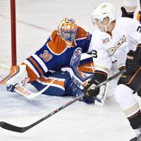 Photo - Anaheim Ducks' Jakob Silfverberg (33) is stopped by Edmonton Oilers' Ben Scrivens (30) during second-period NHL hockey game action in Edmonton, Alberta, Friday, March 28, 2014. (AP Photo/The Canadian Press, Jason Franson)