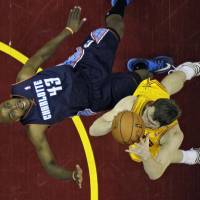 Photo - Charlotte Bobcats' Anthony Tolliver (43) is knocked down by Cleveland Cavaliers' Tyler Zeller in the first half of an NBA basketball game on Saturday, April 5, 2014, in Cleveland. (AP Photo/Mark Duncan)