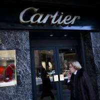 Photo -   In this Sept. 26, 2012 photo, a woman walks by a Cartier jewelry store along Alvear Avenue in the Recoleta neighborhood in Buenos Aires, Argentina. The world's most luxurious designer brands are abandoning Argentina rather than complying with tight new government economic restrictions, leaving empty shelves and storefronts along the capital's elegant Alvear Avenue, where tourists once flocked to see the latest in fashion. (AP Photo/Natacha Pisarenko)