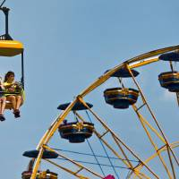 Photo - Visitors to the midway take a ride on the big swing during the 2013 Oklahoma State Fair on Monday, Sep. 16, 2013. Photo by Chris Landsberger, The Oklahoman