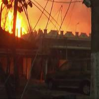 Photo - In this image taken from video, flames rise in the background of houses after a state-owned gas pipeline exploded in Nagaram village, in the southern Indian state of Andhra Pradesh  Friday, June 27, 2014. A top official of the state-run Gas Authority of India Ltd, said more than a dozen people died in the fire following the explosion in the pipeline. (AP Photo/NNIS via AP Video) INDIA OUT