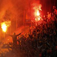 Photo -   Bosnia-Herzegovina fans burn flares during a World Cup Group G qualifying soccer match between Greece and Bosnia-Herzegovina, at Karaiskaki stadium, in Piraeus port, near Athens, Friday, Oct. 12, 2012. (AP Photo/Petros Giannakouris)