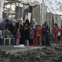 Photo -   Palestinians stand near the rubble of the building of Attia Abu Inkara, a Hamas militant leader, following an Israeli air strike in Rafah refugee camp in southern Gaza Strip, Sunday, Nov. 18, 2012. An Israeli envoy held talks with Egyptian officials Sunday on a ceasefire in his country's offensive on Gaza as Israel widened the range of its targets, striking more than a dozen homes of Hamas militants and two media officials. (AP Photo/Eyad Baba)
