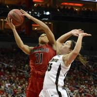 Photo - Louisville's Bria Smith, left, puts a shot up past the defense of Purdue's Courtney Moses during the first half of their second round game in the women's NCAA college basketball tournament in Louisville, Ky., Tuesday March 26, 2013. (AP Photo/Timothy D. Easley)