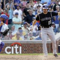 Photo - Colorado Rockies' Charlie Culberson, right, throws his bat after being called out on strikes as Chicago Cubs catcher Welington Castillo celebrates during the ninth inning of a baseball game in Chicago, Thursday, July 31, 2014. The Cubs won 3-1. (AP Photo/Nam Y. Huh)