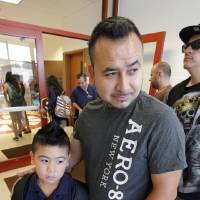 Photo - Gustavo Zambrano waits in line Monday to get into the school office to enroll his son, Nathan, 6, at Prairie Queen Elementary.  PAUL B. SOUTHERLAND - PAUL B. SOUTHERLAND