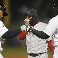 Photo - CORRECTS TO SIXTH INNING, INSTEAD OF FOURTH - Boston Red Sox first baseman Mike Napoli, center, warms his hand through his balaclava as Chicago White Sox's Jose Abreu, left, reaches first and first base coach Daryl Boston during the sixth inning of a baseball game Tuesday, April 15, 2014, in Chicago. Temperatures remained in the mid-30s for the game. (AP Photo/Charles Rex Arbogast)