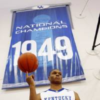 Photo - University of Kentucky freshman Daniel Orton twirls a basketball on his finger as he stands in front of one of the school's national championship banners while waiting for a photo during the team's photo day for the upcoming NCAA college basketball season in Lexington, Ky., Wednesday, Sept. 2, 2009. (AP Photo/Ed Reinke) ORG XMIT: KYER103