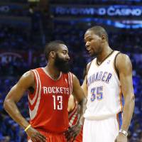 Photo - Houston Rockets guard James Harden (13) talks with Oklahoma City Thunder forward Kevin Durant (35) during a time out in the second quarter of Game 1 of their first-round NBA basketball playoff series in Oklahoma City, Sunday, April 21, 2013. Oklahoma City won 120-91. (AP Photo/Sue Ogrocki)