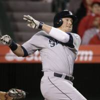 Photo - Seattle Mariners' Justin Smoak follows through on a home run during the ninth inning of a baseball game against the Los Angeles Angels on Wednesday, April 2, 2014, in Anaheim, Calif. (AP Photo/Jae C. Hong)