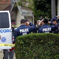 Photo -   Immigration and Customs Enforcement (ICE) agents lining the driveway of a home in Carson, Calif. salute as the body of an ICE agent covered by an American flag is wheeled to a coroner's van on Thursday, May 3, 2012. The 14-year-old son of a federal agent was arrested Thursday in the shooting death of his father in their Southern California home, authorities said. (AP Photo/Nick Ut)