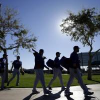 Photo - Texas Rangers pitchers and catchers arrive to the practice field for workouts during spring training baseball practice, Monday, Feb. 17, 2014, in Surprise, Ariz. (AP Photo/Tony Gutierrez)