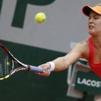 Photo - Canada's Eugenie Bouchard returns the ball during the fourth round match of the French Open tennis tournament against Germany's Angelique Kerber at the Roland Garros stadium, in Paris, France, Sunday, June 1, 2014.  (AP Photo/Michel Euler)