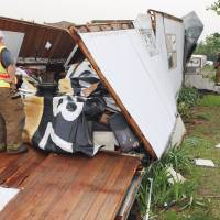 Photo - Firemen help Meshelle Reed look for her missing dog, Lexi, after a storm damaged her home Monday in the Prairie Creek Village mobile home park in Noble.  Photo by Steve Sisney, The Oklahoman