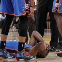 Photo -   Oklahoma City Thunder players stand over teammate James Harden, lower left, after receiving a flagrant double foul from Los Angeles Lakers' Metta World Peace, who was then ejected, in the first half of an NBA basketball game, Sunday, April 22, 2012, in Los Angeles. (AP Photo/Reed Saxon)