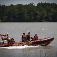 Photo - Malaysian Search and rescue personnel on a speed boat search for passengers of a sunken boat in outskirt of Banting, Malaysia, Wednesday, June 18, 2014. A wooden boat carrying more than 90 Indonesian migrants capsized and sank after leaving Malaysia's west coast, and rescuers scrambled to save more than 60 people still missing, Malaysia's maritime agency said Wednesday. (AP Photo/Vincent Thian)