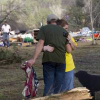 Photo - Russ Butler hugs his wife, Amber, as their friends and neighbors begin the cleanup process in Oak Grove, Ala., Monday, Jan. 23, 2012. At least one person was killed when a suspected tornado swept through the area overnight.  (AP Photo/Dave Martin) ORG XMIT: ALDM101