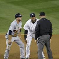 Photo -   New York Yankees' Robinson Cano, center, complains to umpire Jeff Nelson after Nelson called Detroit Tigers' Omar Infante, left, safe at second base in the eighth inning of Game 2 of the American League championship series Sunday, Oct. 14, 2012, in New York. (AP Photo/Kathy Willens)