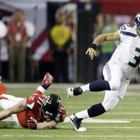 Photo - Seattle Seahawks quarterback Russell Wilson (3) runs past Atlanta Falcons defensive end Kroy Biermann (71) during the first half of an NFC divisional playoff NFL football game Sunday, Jan. 13, 2013, in Atlanta. (AP Photo/David Goldman)