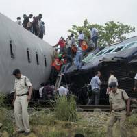 Photo - Indian officials and rescuers gather around the wreckage after the Gorakhpur Express passenger train slammed into a parked freight train Chureb, near Basti, Uttar Pradesh state,, India, Monday, May 26, 2014. According to officials dozens were killed. (AP Photo)