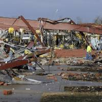 Photo -   An employee of Henryville High School examines the remains of the building following severe storms Friday, March 2, 2012, in Henryville, Ind. Tornadoes ripped across several small southern Indiana towns on Friday, killing at least three people and leaving behind miles of flattened devastation along the border with Kentucky. (AP Photo/Timothy D. Easley)
