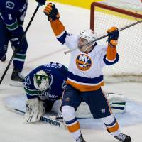 Photo - New York Islanders' Casey Cizikas, right, celebrates after Matt Martin scored the team's fifth goal as Vancouver Canucks' goalie Eddie Lack, of Sweden, kneels on the ice during third period NHL hockey action in Vancouver, British Columbia, on Monday March 10, 2014. (AP Photo/The Canadian Press, Darryl Dyck)