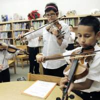 Photo - From left, Amy Barron, Hannah Geeslin and Saul Ortiz play violins during a mariachi class Tuesday at Fillmore Elementary School in Oklahoma City. Photos by Paul Hellstern, The Oklahoman