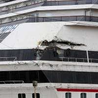 Photo - The Carnival cruise ship Triumph is damaged after the being dislodged from its mooring at BAE shipyard during high winds Wednesday, April 3, 2013 in Mobile, Ala. Triumph was disabled Feb. 10 by an engine fire that stranded thousands of passengers onboard for days in the Gulf. It was towed into port in Mobile. (AP Photo/AL.com, Bill Starling)  MAGS OUT