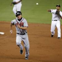 Photo -   Atlanta Braves' Chipper Jones, foreground, is thrown out by Miami Marlins second baseman Donovan Solano as he runs back to first base after a sacrifice fly by Freddie Freeman during the third inning of a baseball game, Wednesday, Sept. 19, 2012, in Miami. Martin Prado scored on the play. (AP Photo/Wilfredo Lee)