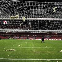 Photo - Pieces of debris fallen from the roof of the stadium rest over the pitch and the goal's net, prior the Portuguese league soccer match between Benfica and Sporting at Benfica's Luz stadium, in Lisbon, Sunday, Feb. 9, 2014. Strong winds damaged the stadium roof before kick off and debris fell on the pitch and stands. It was decided the match should be postponed for security reasons. (AP Photo/Francisco Seco)