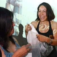 Photo - Karen Arellano, right, laughs as she smells shirts with her friend Christina Lopez during a pheromone party, Friday, June 15, 2012, in Los Angeles. The get-togethers, which have been held in New York and Los Angeles and are planned for other cities, require guests to submit a slept-in T-shirt that will be sniffed by other participants. Then you can pick your partner based on scent. (AP Photo/Mark J. Terrill)