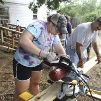 Photo -  Anna Tipton, 17, of Muldrow, and Manuel Aguilar work on a ramp as part of Youth Force Cleveland County, a mission project hosted by Goodrich Memorial United Methodist Church in Norman. PHOTO BY DAVID MCDANIEL, THE OKLAHOMAN   David McDaniel