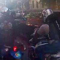 Photo - In this frame grab from video provided by the New York Police Department, motorcyclists ride alongside a sport utility vehicle, Sunday, Sept. 29, 2013, in New York. Police say that a man driving with his family along a New York City highway was attacked and beaten by a large group of motorcyclists who first surrounded his sport utility vehicle and stopped it on the road, then chased him for miles after he plowed through the blockade of bikes in an attempt to escape. (AP Photo/New York Police Department)