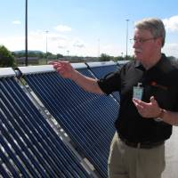 Photo - Charlie Slavik, marketing and sales vice president for Indianapolis-based Solar America Solutions, discusses the workings of a solar panel array atop a prison building at Ross Correctional Institution on Wednesday, July 16, 2014, in Chillicothe, Ohio. Slavik says the panels are about both being green and giving inmates trained to install and maintain them a second chance. (AP Photo/Andrew Welsh-Huggins)