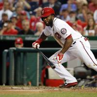 Photo - Washington Nationals' Denard Span bunt during the third inning of a baseball game against the Cincinnati Reds at Nationals Park on Tuesday, May 20, 2014, in Washington. Span reached first and made it all the way to third on an error on the play. (AP Photo/Alex Brandon)