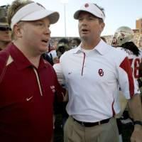Photo - Florida State defensive coordinator Mark Stoops meets with his older brother, OU coach Bob Stoops, after Oklahoma's 47-17 rout of the Seminoles at the Gaylord Family-Oklahoma Memorial Stadium on Saturday, Sept. 11, 2010, in Norman, Okla. Photo by Bryan Terry, The Oklahoman.