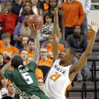 Photo - Oklahoma State 's Kamari Murphy (21) defends on South Florida Bulls' Jawanza Poland (5) during the college basketball game between Oklahoma State University (OSU) and the University of South Florida (USF) on Wednesday , Dec. 5, 2012, in Stillwater, Okla.   Photo by Chris Landsberger, The Oklahoman