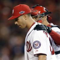 Photo -   Washington Nationals catcher Kurt Suzuki, back, speaks with starting pitcher Gio Gonzalez after Gonzalez walked St. Louis Cardinals' Shane Robinson in the fifth inning of Game 5 of the National League division baseball series on Friday, Oct. 12, 2012, in Washington. (AP Photo/Pablo Martinez Monsivais)