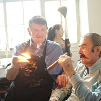 Photo - Chef John Bennett lights a cigar for LeRoy Neiman during his 90th birthday party last year.  PHOTO PROVIDED BY JOHN SIMON