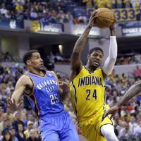 Photo - Indiana Pacers forward Paul George (24) cuts in front of Oklahoma City Thunder guard Thabo Sefolosha as he drives the lane in the second half of an NBA basketball game in Indianapolis, Sunday, April 13, 2014. The Pacers defeated the Thunder 102-97. (AP Photo/Michael Conroy)