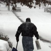 Photo -   FILE - In this Dec. 19, 2009 file photo, Bill Winterle carries his neighbor's newspaper to her doorstep while shoveling his driveway during a major winter storm in Havertown, Pa. The storm hit the Mid-Atlantic and East coast areas. Securing your home and making it look occupied while you are away, and making sure packages and newspapers aren't sitting in your driveway day after day will help deter thieves. (AP Photo/Jacqueline Larma, File)