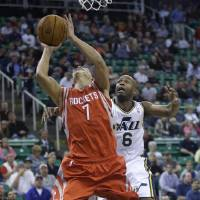 Photo - Houston Rockets' Jeremy Lin (7) goes to the basket as Utah Jazz's Jamaal Tinsley (6) defends in the first quarter during an NBA basketball game Saturday, Nov. 2, 2013, in Salt Lake City.  (AP Photo/Rick Bowmer)
