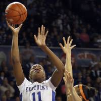 Photo - Kentucky's DeNesha Stallworth (11) shoots under pressure from Tennessee's Cierra Burdick during the first half of an NCAA college basketball game at Memorial Coliseum in Lexington, Ky., Sunday, March 3, 2013. (AP Photo/James Crisp)