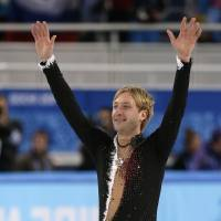Photo - Evgeny Plyushchenko of Russia waves to spectators after competing in the men's team short program figure skating competition at the Iceberg Skating Palace during the 2014 Winter Olympics, Thursday, Feb. 6, 2014, in Sochi, Russia. (AP Photo/Bernat Armangue)