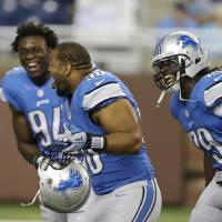 Photo - Detroit Lions defensive end Ezekiel Ansah (94), defensive tackle Ndamukong Suh (90) and defensive end Willie Young (79) laugh as players warm up for an NFL football game between the Lions and the Minnesota Vikings in Detroit, Sunday, Sept. 8, 2013. (AP Photo/Carlos Osorio)