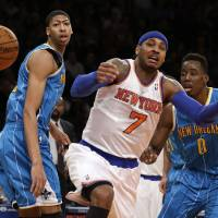 Photo - New Orleans Hornets forward Anthony Davis, left, watches as New York Knicks forward Carmelo Anthony (7) loses the ball in the first half of their NBA basketball game at Madison Square Garden in New York, Sunday, Jan. 13, 2013. Hornets forward Al-Farouq Aminu (0) looks on. (AP Photo/Kathy Willens)