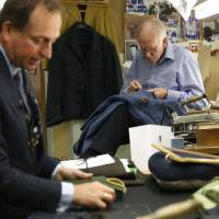 Photo - In this photo taken Friday, June 6, 2014, a tailor, right, works on a suit as Simon Cundey, managing director of Henry Poole & Co tailor, the first shop to set up in Savile Row in 1846, speaks to Associated Press at his store on Savile Row in London. In the world of women's fashion, London often seems to play second fiddle to other style capitals: It lacks the allure of Paris's haute couture, or the polish of Milan's luxury labels. But it's a whole different story when it comes to dressing men. Steeped in a rich history of tailoring for kings, army generals and the world's wealthiest men, London is now marketed as the home of men's fashion - the original birthplace of the tuxedo jacket, the bowler hat and the three-piece suit, among other classic items. When trendy designers like Alexander McQueen and Burberry kick off the new season's menswear shows in the British capital Sunday, the catwalks will be staged just blocks away from elite tailoring houses that have been perfecting their craft for over a century. Savile Row, a street lined with more than a dozen tailors and a living museum of the English love affair with luxury menswear, has a long-standing tradition closely tied to a history in royal dress, military uniforms and gentry sports like horseback riding and hunting. (AP Photo/Sang Tan)