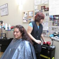 Photo - Alejandra Ordonez gets her hair washed and styled by Ingrid Valas, a Francis Tuttle cosmotology student during the Single Parent Support Network's recent